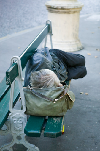 Unrecognizable person sleeping on bench on sidewalk, elevated view